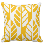 Yellow throw pillow with white leaves pattern