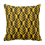 Yellow throw pillow with black leaves pattern